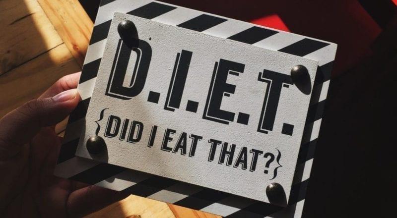 Un signo de dieta sostenido por alguien que conoce la importancia de los requisitos dietéticos